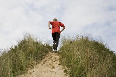 ascends: Man running up grassy hillside
