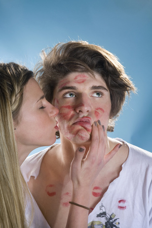 Young man being kissed all over by girl