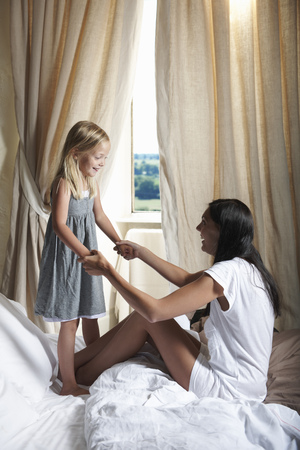 Mother and daughter playing on bed LANG_EVOIMAGES