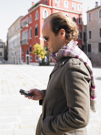 scarves: Man looking at his phone in the street