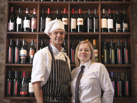 selections: Chef and waitress standing with wine LANG_EVOIMAGES