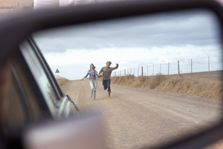 pursued: Couple running behind car