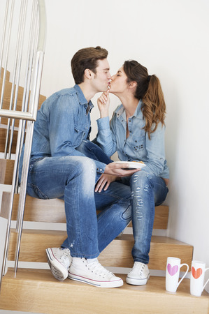 snacking: Couple kissing on stairs
