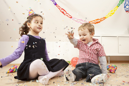 in twos: Little boy and girl with confetti