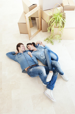 equivalents: Laughing couple laying on floor together
