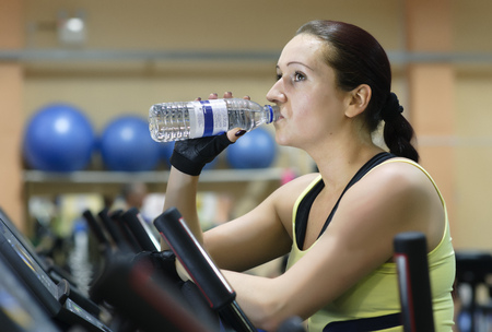 refreshed: Woman drinking water at gym LANG_EVOIMAGES