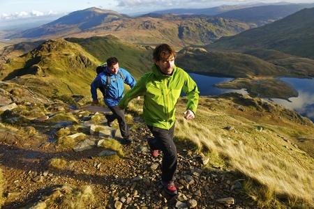 pursuing: Men hiking on rocky mountainside