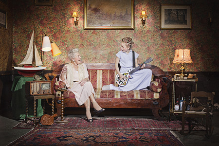 Girl playing guitar for grandmother