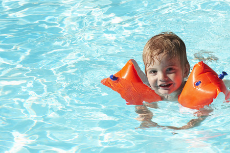 spirited: Baby boy swimming with water wings