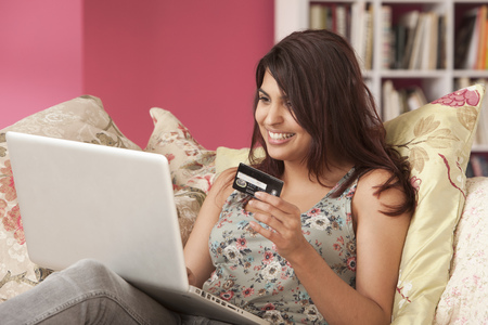 Young woman with credit card at laptop