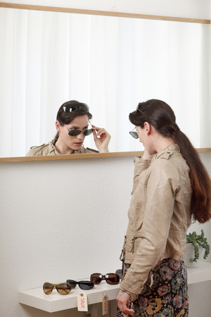 browses: woman trying on sunglasses in mirror