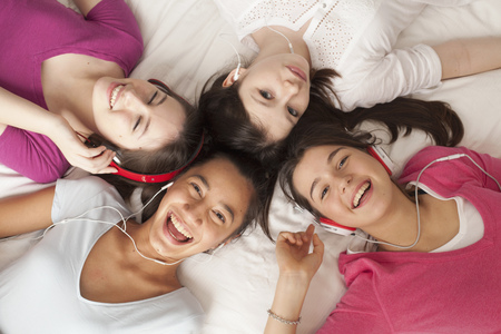 teenage girls lying on floor listening to music,smiling