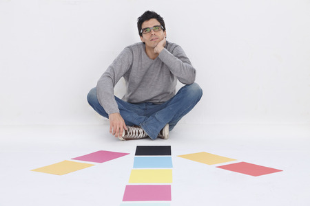 resolving: Man sitting with coloured paper,smiling
