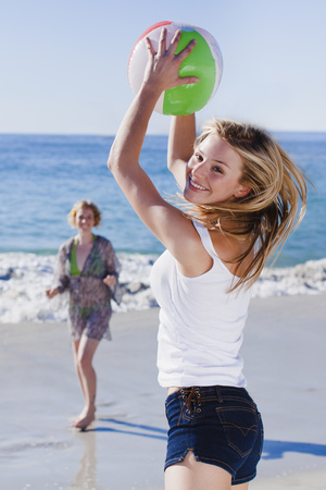 Women playing with ball on beach