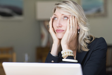 indecisive: Frustrated businesswoman using laptop