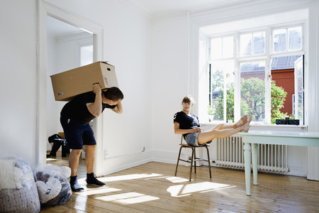 Woman watching boyfriend carry heavy box