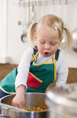 Toddler girl cooking in kitchen