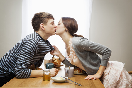 ecstasy: Woman kissing boyfriend over table LANG_EVOIMAGES