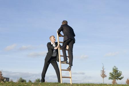 Businessman holding ladder for colleague LANG_EVOIMAGES