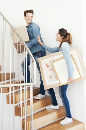 in twos: Couple moving boxes upstairs in new home LANG_EVOIMAGES