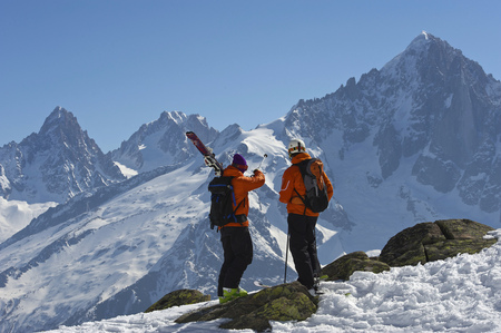 Skiers admiring snowy mountain view LANG_EVOIMAGES