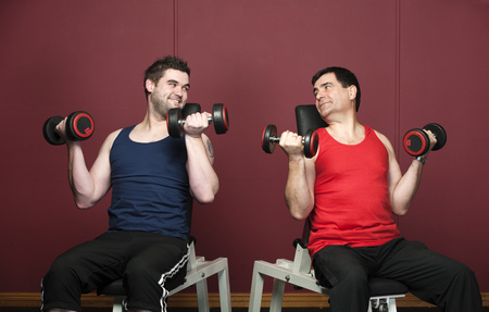 levantar peso: Men lifting weights together in gym