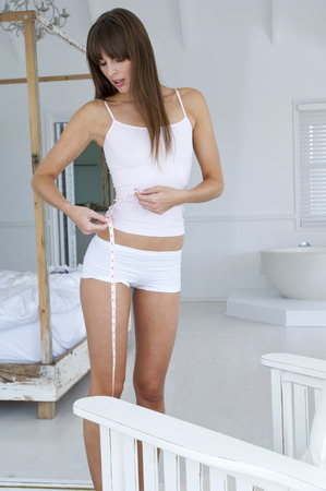 Woman measuring her waist LANG_EVOIMAGES