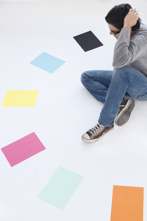strategize: Man looking at different coloured paper,white background LANG_EVOIMAGES