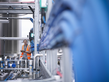manufacturer: Worker with machinery in bottling plant