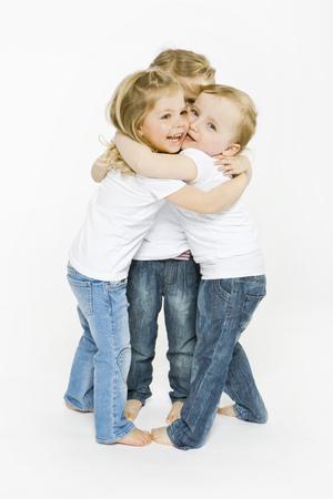 equivalents: Three toddler girls hugging LANG_EVOIMAGES