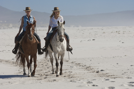 move in: 2 people riding horses on the beach LANG_EVOIMAGES