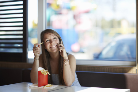 Woman with Frenchfries and Cellphone