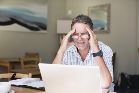 Frustrated businessman using laptop