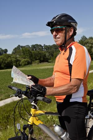 resolving: Biker reading map on rural road