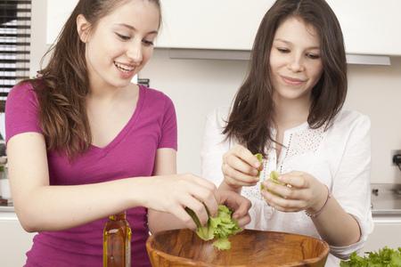 pubescent: teenage girls preparing salad in kitchen LANG_EVOIMAGES