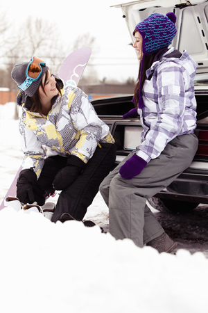 snowed: Teens sitting on car with snowboard