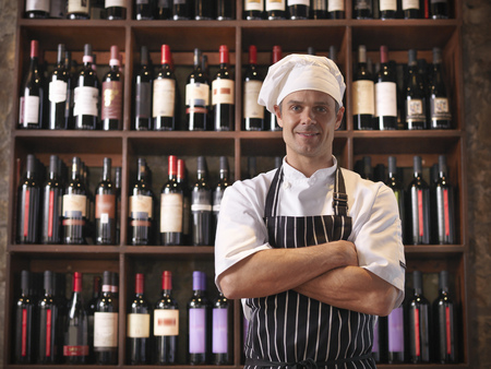 large group of business people: Chef standing with shelves wine
