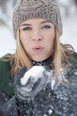 Woman blowing handful of snow