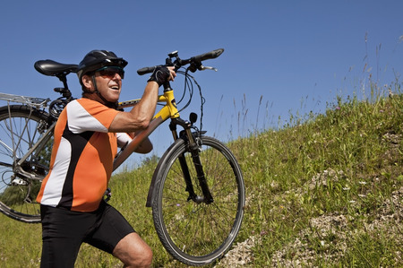 Man carrying bicycle on grassy hillside LANG_EVOIMAGES