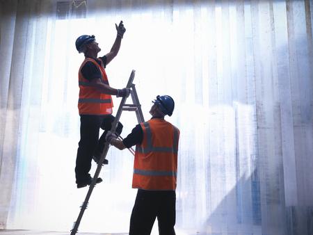 scaling ladder: Worker holding ladder for colleague LANG_EVOIMAGES