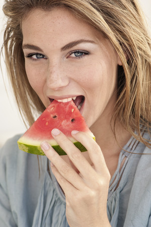 snacking: Woman eating watermelon