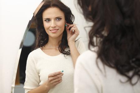 woman trying on earrings