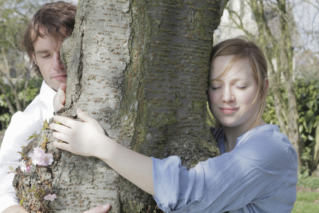 mischeif: Couple hugging tree in park LANG_EVOIMAGES