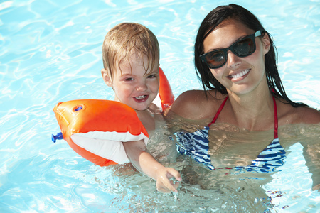 safe water: Mother and son playing in swimming pool