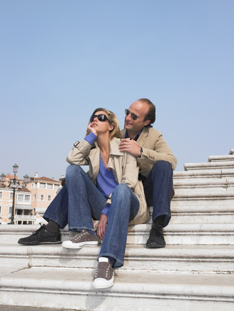 sightseers: Couple on stairs by the marina