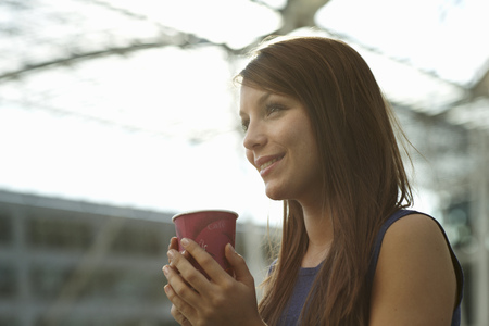 rejoices: Woman with coffecup smiling