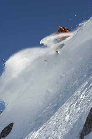 jeopardizing: Skier turning on steep mountain face LANG_EVOIMAGES