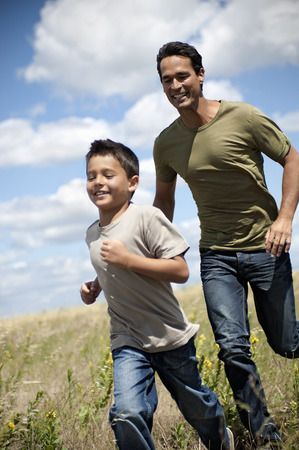pursuing: Father and son running through a field LANG_EVOIMAGES