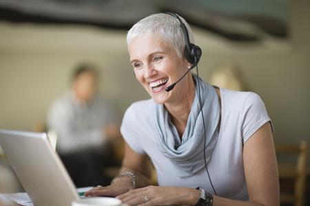 reconocimientos: Mujer mayor en auriculares con ordenador portátil