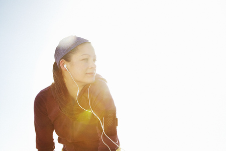 musically: Portrait of sporty woman with lens flare